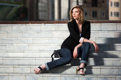 Young fashion woman sitting on the steps Royalty Free Stock Photography