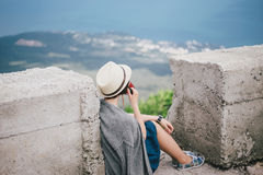 Young fashion woman sitting on a top of the mountain drinking tea with beautiful mountains and ocean view on the background Stock Photos