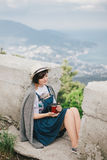 Young fashion woman sitting on a top of the mountain drinking tea with beautiful mountains and ocean view on the background Royalty Free Stock Photo