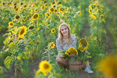 Young fashion woman with a sun flowers and in stylish hat and blue jeans shorts Royalty Free Stock Photos