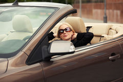 Young fashion woman in sunglasses in a car Royalty Free Stock Image