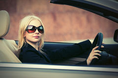 Young fashion woman in sunglasses driving car Stock Photo