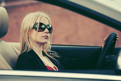 Young fashion woman in sunglasses driving car Stock Image