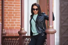 Young fashion woman in black leather jacket leaning on railing Royalty Free Stock Images