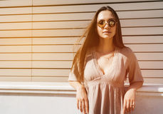 Young fashion woman in sunglasses posing outdoor over wooden bac Royalty Free Stock Photos