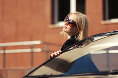 Young fashion woman in sunglasses standing by her car Stock Photo