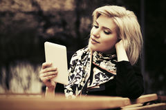 Young fashion woman with tablet computer sitting on bench Royalty Free Stock Photography
