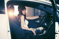 Young fashion woman in tank top sitting in a car Royalty Free Stock Images