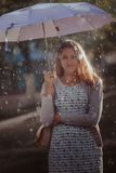 Young fashion woman with umbrella.  Filtered image with blurry rain Stock Photography