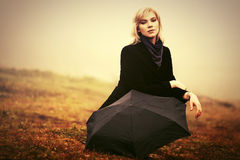 Young fashion woman with umbrella in a fog outdoor Stock Photo