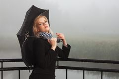 Young fashion woman with umbrella leaning on handrail in a fog. Outdoor stock images