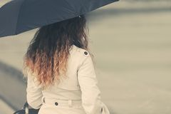 Fashion woman in white trench coat with umbrella. Young fashion woman with umbrella walking on city street Stylish female model with long curly hairs wearing stock photos