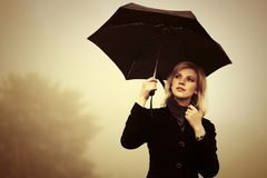 Young fashion woman with umbrella walking in a fog outdoor. Young fashion blond woman with umbrella walking in a fog outdoor Stock Photo