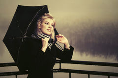 Young fashion woman with umbrella walking by the lake in a fog. Young fashion blond woman with umbrella walking by the lake in a fog Royalty Free Stock Photography