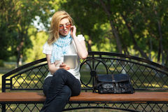 Young fashion woman using tablet computer in park Royalty Free Stock Images