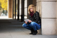 Young fashion woman using tablet computer at the wall Royalty Free Stock Image