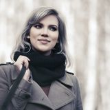Young fashion woman in beige coat walking in autumn city park stock photo