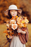 Young fashion woman  walking in autumn park with a bouquet of fa Stock Image