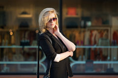 Young fashion business woman in sunglasses walking on city street Royalty Free Stock Image