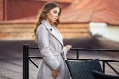 Young fashion woman in light grey coat walking in city street Royalty Free Stock Photos