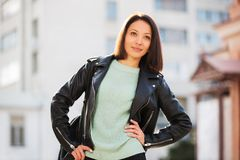 Young fashion woman in black leather jacket walking in city street Stock Photography