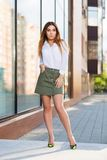 Young fashion woman in white blouse and short skirt in city street. Young fashion woman walking in  city street. Stylish female model wearing white blouse and Royalty Free Stock Images