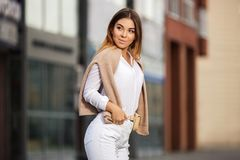 Young fashion woman in white shirt and ripped jeans walking in city street Royalty Free Stock Photography