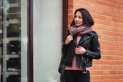 Young fashion woman wearing black leather jacket looking at window display. Young fashion woman looking at window display Stylish female model wearing black Stock Image