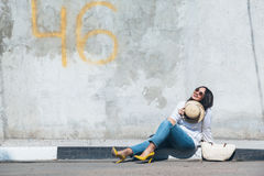 Plus size model. Young fashion woman wearing ripped jeans, colorful heel shoes and straw accessories posing over gray concrete city wall. Plus size model Royalty Free Stock Image