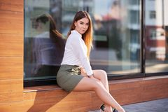 Young fashion woman wearing white shirt and short skirt at the mall. Young fashion woman sitting on the mall window in city street. Stylish female model wearing Royalty Free Stock Photos