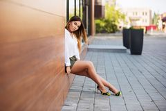 Young fashion woman in white blouse and short skirt at the mall. Young fashion woman sitting on the mall window in city street. Stylish female model wearing Royalty Free Stock Photography
