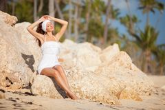 Young fashion woman in white relax on the beach stones. Happy tropical lifestyle. White sand, blue sky and crystal sea of beach. royalty free stock photos