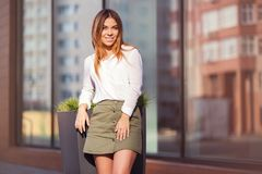 Young fashion woman in white shirt and short skirt in city street. Young fashion woman standing next to mall window in city street Stylish female model in white Stock Photography