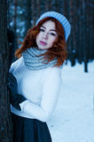 Young fashion woman in winter forest. Young fashion girl red head in winter forest Royalty Free Stock Image
