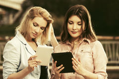 Young fashion women using tablet computer outdoor Royalty Free Stock Photos