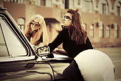 Young fashion women by vintage car in city street Stock Images