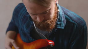 Young fashionable Bearded hipster playing guitar playing melody bass guitar stock footage