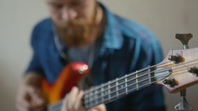Young fashionable Bearded hipster playing guitar playing melody bass guitar stock video