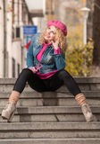 Young fashionable beautiful girl with pink cap looking around in the city Royalty Free Stock Images