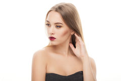 Young fashionable blonde woman with gorgeous smokey makeup touching her hear posing with bare shoulders on white studio background Stock Photo