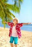 Young fashionable boy enjoys life on tropical beach Stock Photos