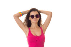 Young fashionable brunette girl in pink sunglasses and shirt posing on camera isolated on white background Royalty Free Stock Photo