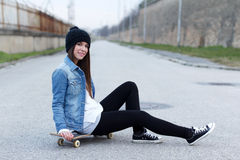 Young fashionable brunette skateboarder girl Stock Photo