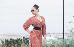 Young fashionable brunette woman wearing long dress in sunglasses posing near sea, pier with yachts. Young fashionable brunette woman wearing long red summer Stock Images