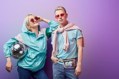 Young fashionable couple of dancers posing with disco ball on violet background stock photography