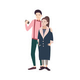 Young fashionable couple of man and woman dressed in stylish clothes embracing and making selfie on smartphone. Concept Royalty Free Stock Images