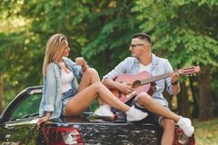 Modern couple taking a break on road trip and enjoying their favorite song. Young fashionable couple playing acoustic guitar on the back side of their stock photo