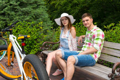 Young fashionable couple sitting on bench near bikes in park Royalty Free Stock Photo