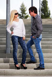 Young fashion man and woman on the steps Royalty Free Stock Photo
