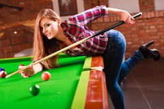 Young fashionable girl playing billiard. Competition concept. Young girl having fun with billiard. Beautiful fashionable woman playing spending time on Stock Image
